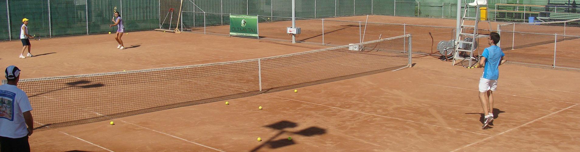 Copii antrenandu-se pe un teren de tenis sub indrumarea antrenorului