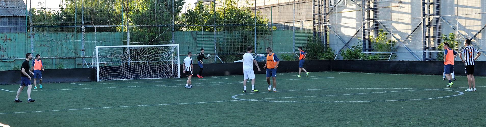 Baieti jucand fotbal pe un teren sintetic de fotbal in incinta clubului Popeci din Craiova