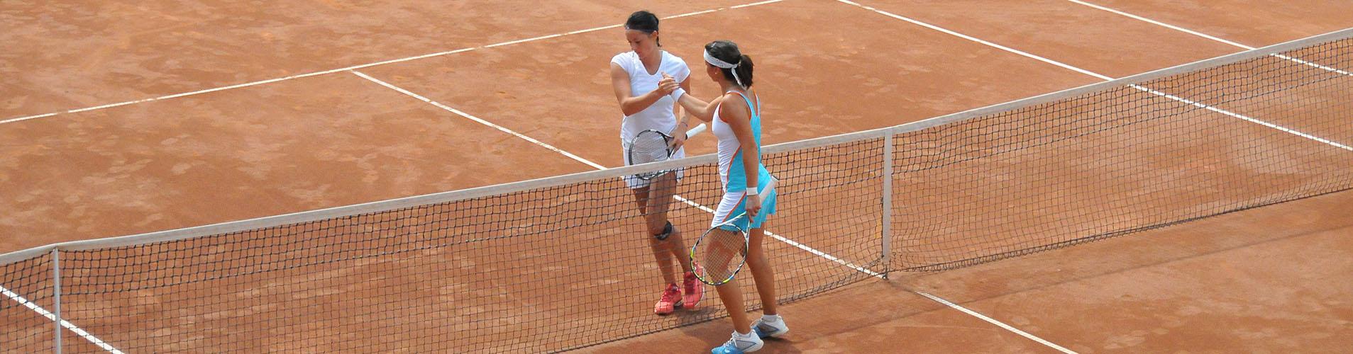 2 jucatoare de tenis terminand un meci de tenis pe terenul de zgura din Clubul Popeci