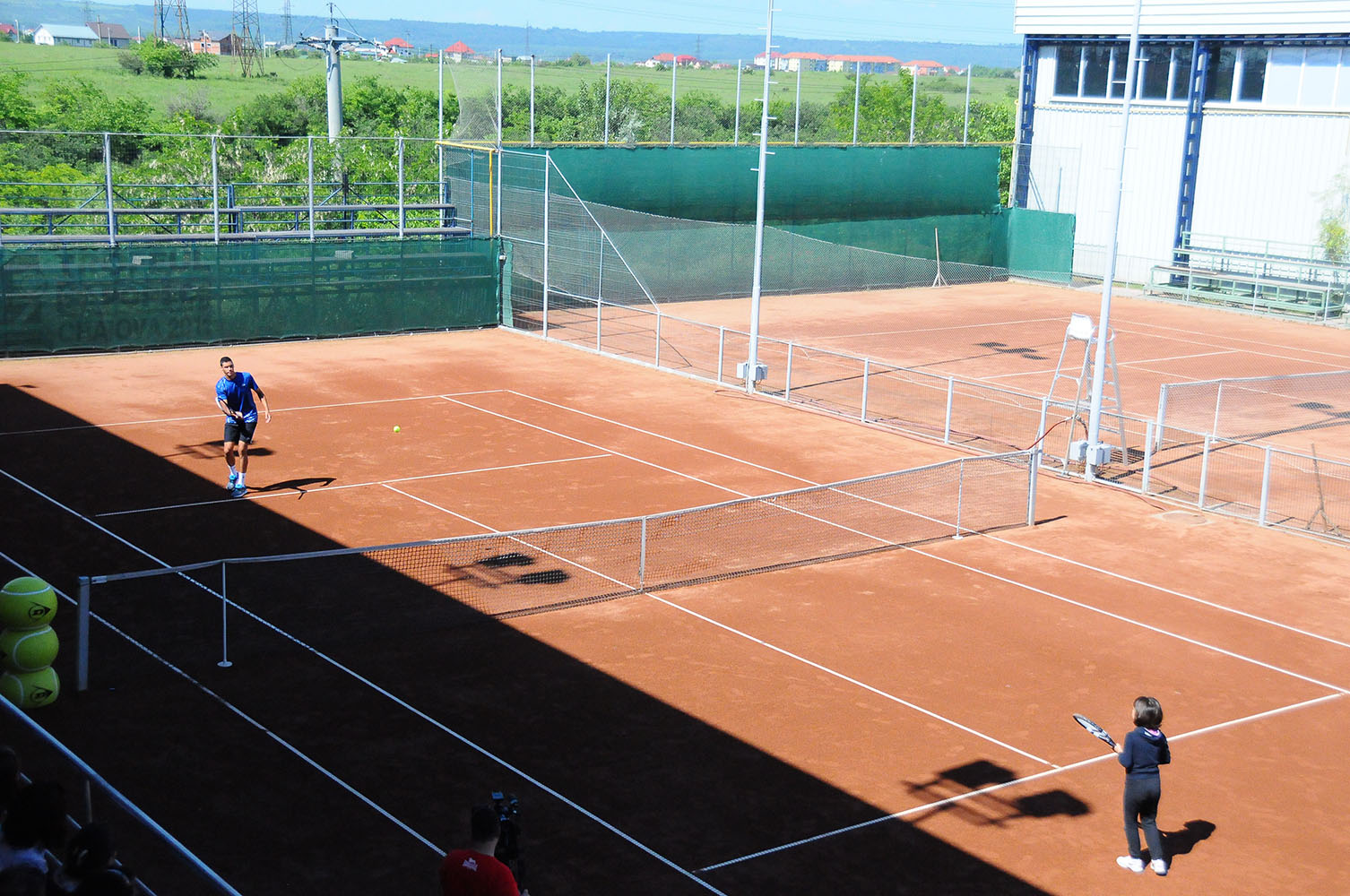 2 jucatori de tenis pe un teren de zgura
