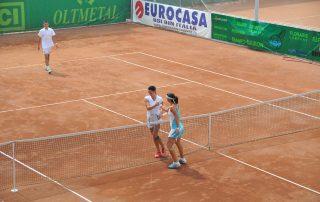 2 jucatoare de tenis pe un teren de zgura